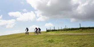 Three mountain cyclists almost silhouetted on a ridge of a hill in the South Downs, England, UK while cycling the South West Way